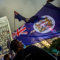 Demonstrators wave the former flag of British Hong Kong during a rally in Hong Kong in 2019.