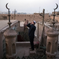 A Uyghur muezzin calls the evening prayer from the rooftop of a mosque in Kashgar, China.  | ADAM DEAN / THE NEW YORK TIMES