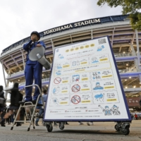 Measures to prevent novel coronavirus infections are illustrated on a sign in front of Yokohama Stadium in October 2020. | KYODO