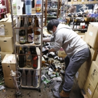 Bottles are scattered on the floor at a liquor shop in the city of Fukushima where a powerful earthquake hit on Feb. 13. The city announced its first fatality due to the quake on Thursday.
