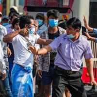A military supporter points a sharp object as he confronts pro-democracy protesters in Yangon, Myanmar, on Thursday.  | REUTERS