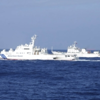 A Chinese marine surveillance ship cruises next to a Japan Coast Guard patrol ship in the East China Sea near the disputed isles known as Senkaku Islands in Japan and Diaoyu Islands in China, in February 2013.