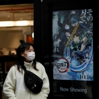 People walk past a poster for the animated movie 'Demon slayer' in December. | REUTERS
