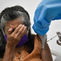 An older woman is inoculated against COVID-19 with the Sinovac vaccine, at the San Miguel nursing home in Cali, Colombia, on Thursday. |  AFP-JIJI