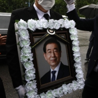 A man holds a portrait of deceased Seoul Mayor Park Won-soon during a funeral service in Seoul on July 13, 2020. | BLOOMBERG