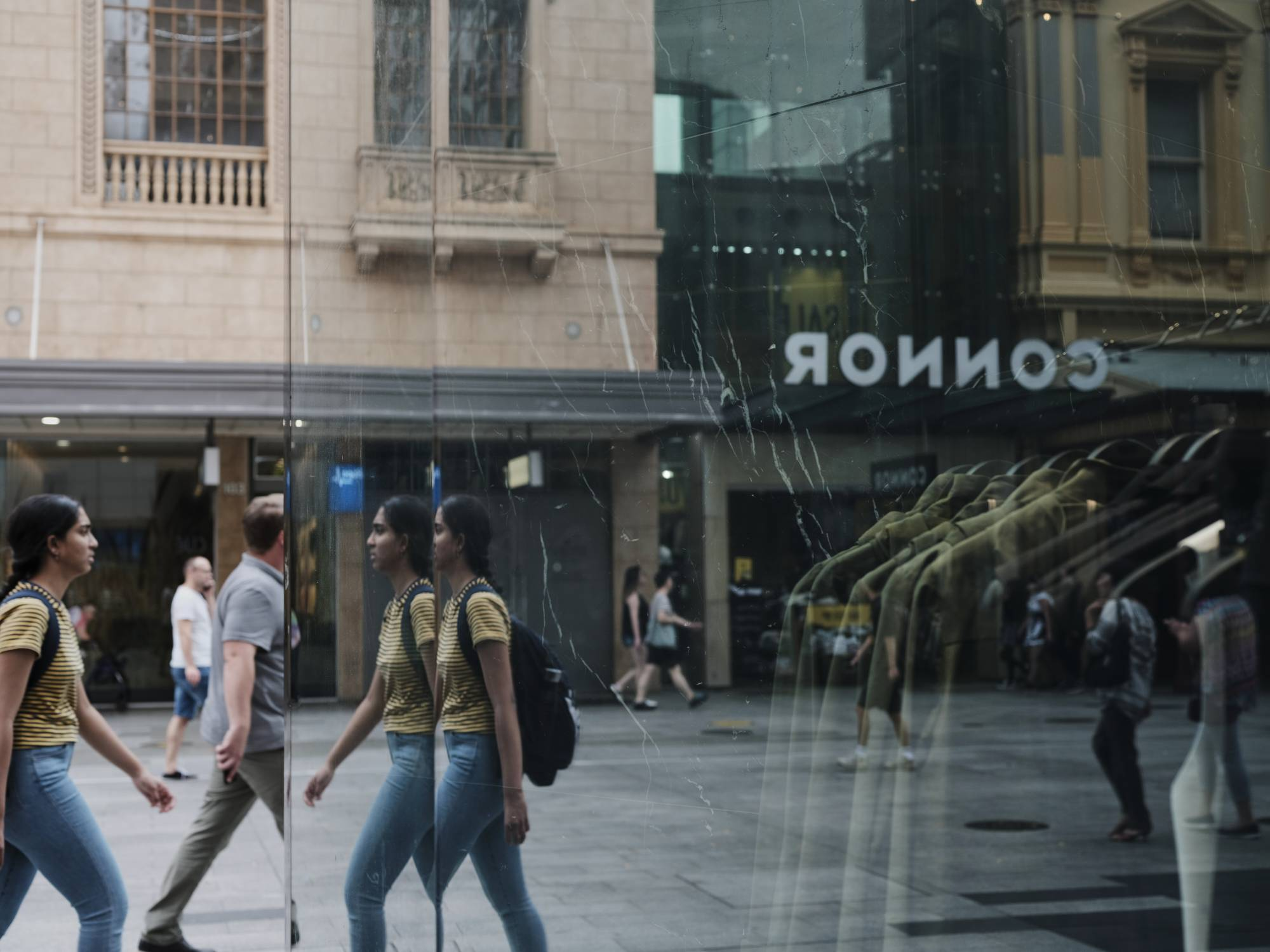Shoppers and pedestrians are reflected in a store window at Rundle Mall in Adelaide, Australia, on Feb. 11.   BLOOMBERG