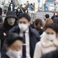 People walk in the Shinjuku district of Tokyo earlier this month. | KYODO