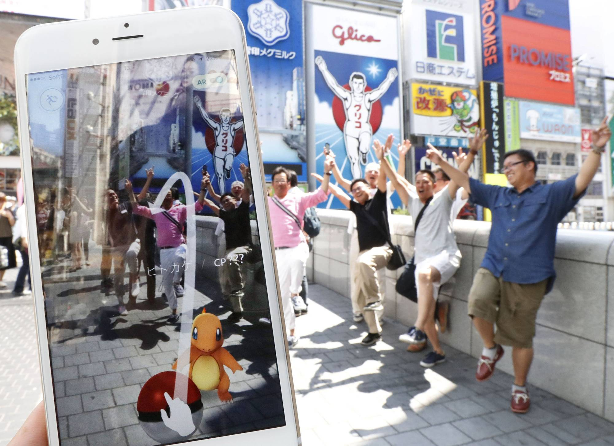 People play Pokemon Go in the Minami district of Osaka on July 22, 2016, the day the game debuted in Japan. | KYODO