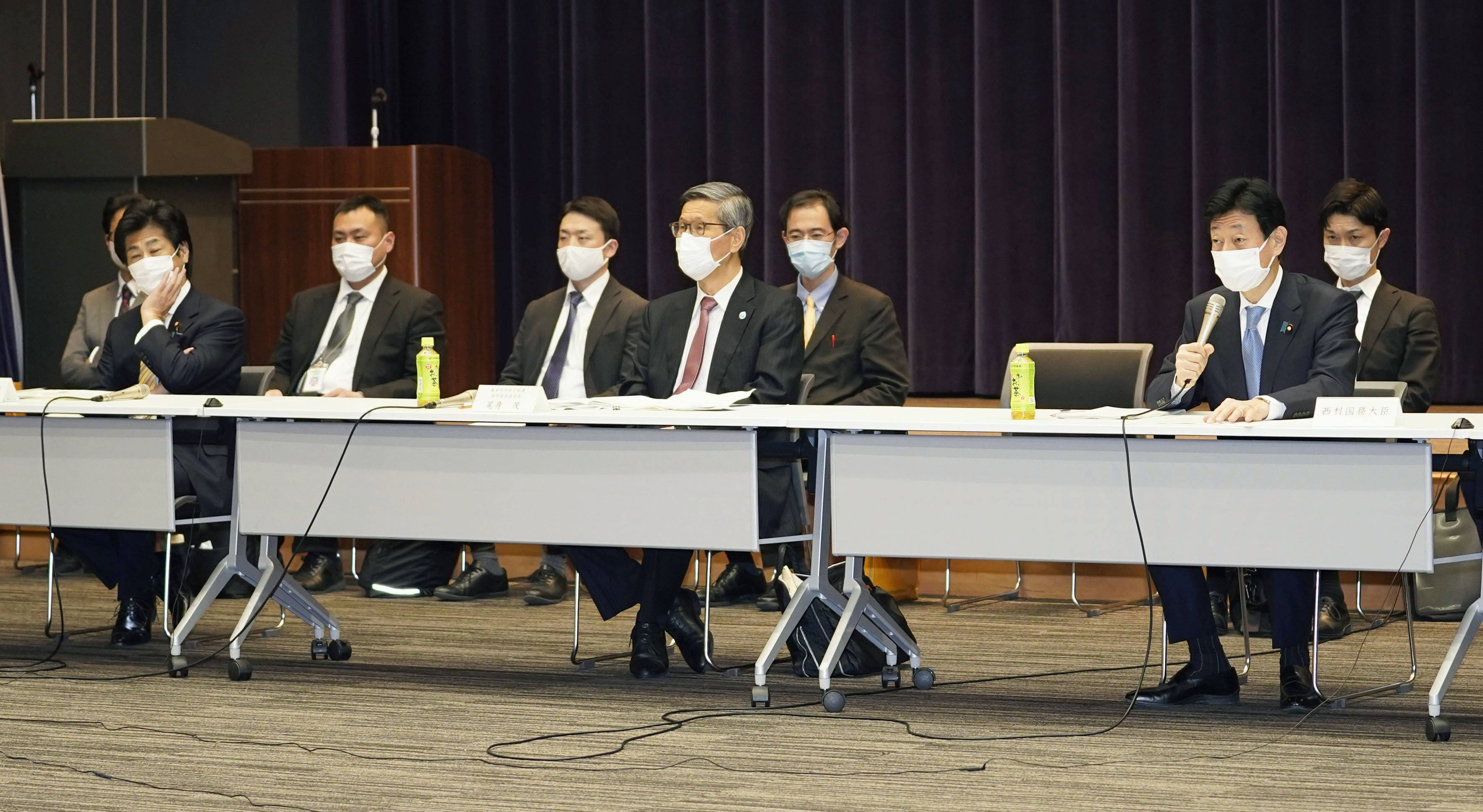 Yasutoshi Nishimura (right), the minster leading the government's pandemic response, attends an advisory panel with Shigeru Omi (center), the panel's head, and health minister Norihisa Tamura (left) in Tokyo on Friday. | KYODO