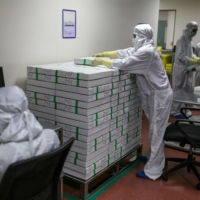 Employees stack packed vials of Covishield, the local name for the COVID-19 vaccine developed by AstraZeneca, at the Serum plant in Maharashtra, India, on Jan. 22. | BLOOMBERG