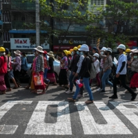 Demonstrators rally against the military coup and show their support to local residents Friday in the Tamwe neighborhood of Yangon, after riot police officers used teargas the previous night to disperse a crowd of protesters. | REUTERS