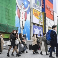 People walk in the Minami district of Osaka on Tuesday.