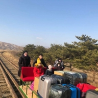 Russian diplomats and family members use a hand-pushed rail trolley to leave North Korea amid coronavirus restrictions while crossing the demarcation line between North Korea and Russia on Thursday.  | RUSSIAN FOREIGN MINISTRY / VIA REUTERS