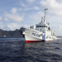 A Japan Coast Guard vessel sails in front of Uotsuri Island, one of the disputed Senkaku islets in the East China Sea, in August 2013. | REUTERS