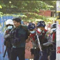 A photo provided by a protester shows Yuki Kitazumi being detained by Myanmar security police in Yangon on Friday. | KYODO