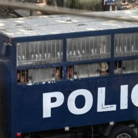 Protesters make three-finger salutes from a police truck in Yangon on Saturday.    AFP-JIJI