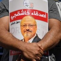 Friends of murdered Saudi journalist Jamal Khashoggi hold posters bearing his picture as they attend an event marking the second anniversary of his assassination, in front of Saudi Arabia's Consulate in Istanbul last October.  | AFP-JIJI