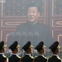 People's Liberation Army soldiers stand before a giant screen as Chinese President Xi Jinping speaks during a military parade marking the 70th founding anniversary of People's Republic of China on Oct. 1, 2019, in Beijing. | REUTERS