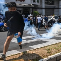 Protesters run after police fired tear gas to disperse them during a demonstration against the military coup in Yangon on Sunday.    AFP-JIJI