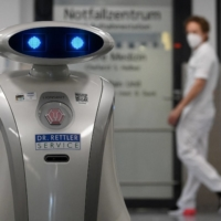 Worker robot 'Franzi' cleans a hospital in Munich Neuperlach, Germany, on Feb. 12. Perhaps no single aspect of the digital revolution has received more attention than the effect of automaton on jobs, work, employment and incomes. | AFP-JIJI