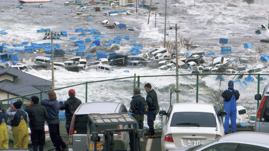 The creeping wave: Residents of Miyako, Iwate Prefecture, watch helplessly as a wave approaches via the Heigawa estuary after the earthquake on March 11, 2011.