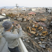 A man surveys the damage in Ishinomaki, Miyagi Prefecture, a few days after the city was struck by a deadly tsunami in March 2011. | KYODO