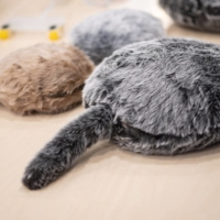 Qoobo (front) and petit Qoobo robots from Yukai Engineering take the form of fluffy pillow with tails that move. | AFP-JIJI