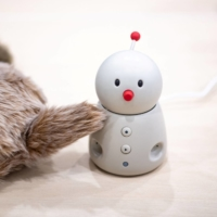 Seen with a petit Qoobo (left), snowman-like Bocco emo allows users to sent and receive voice messages through their telephones. | AFP-JIJI