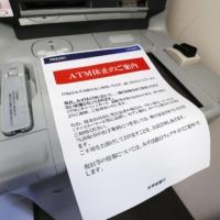 A notice explaining that ATMs are still not in service is placed on a machine at a Mizuho Bank in Chuo Ward, Tokyo, on Monday. | KYODO