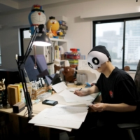 Kamentotsu, who goes by a pseudonym and wears a mask in media appearances, found himself approached by 40 publishing companies after posting his first manga strip online. | REUTERS
