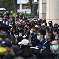 Supporters wait outside a court in Hong Kong on Monday, ahead of hearings for dozens of dissidents charged with subversion in the largest use yet of Beijing's sweeping new national security law.  | AFP-JIJI