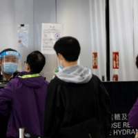 Airport staff members line up to collect novel coronavirus testing kits at Hong Kong International Airport last month.