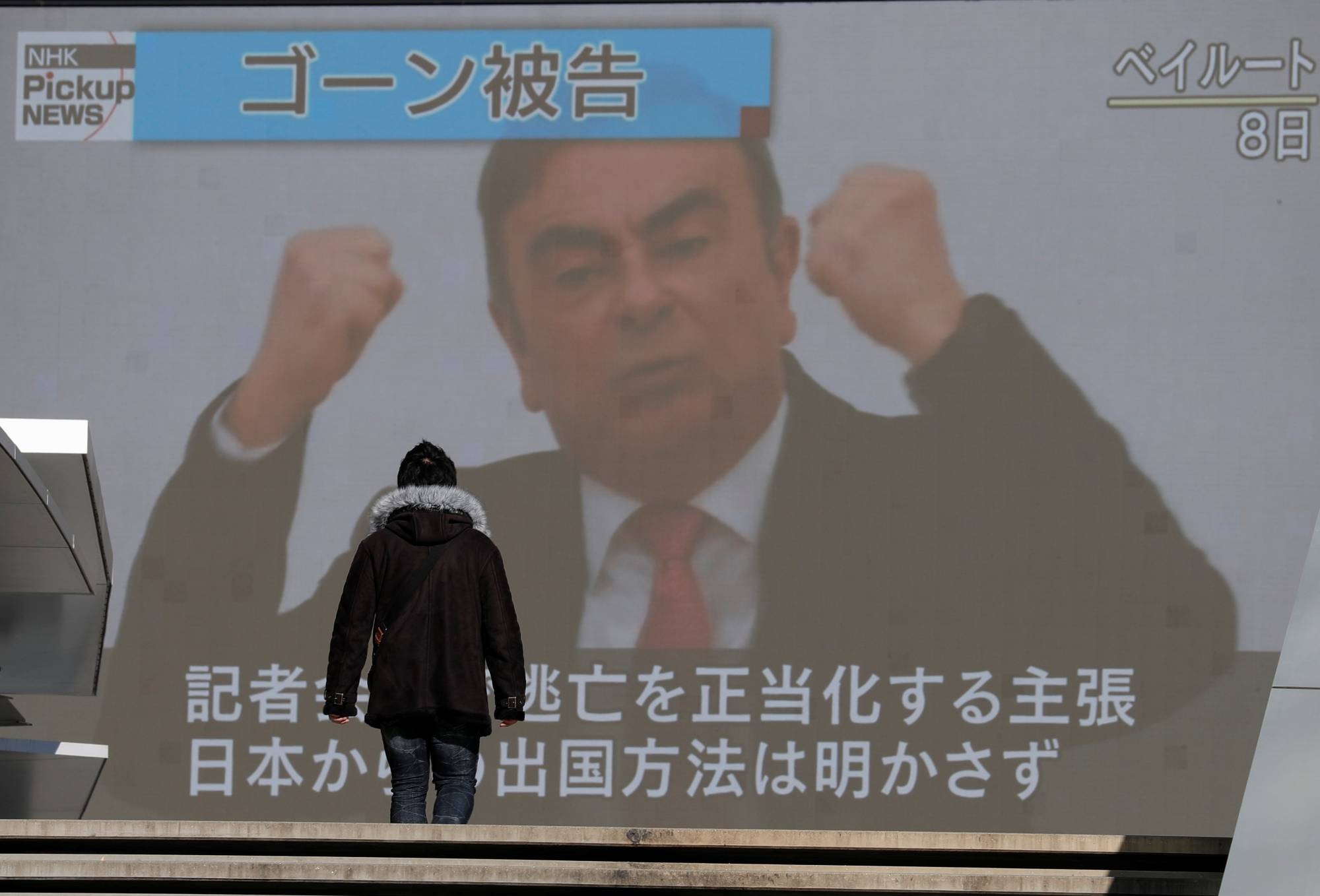 A passerby walks in front of a huge street monitor in Tokyo broadcasting a news conference by former Nissan chief Carlos Ghosn in Beirut on Jan. 9, 2020. | REUTERS
