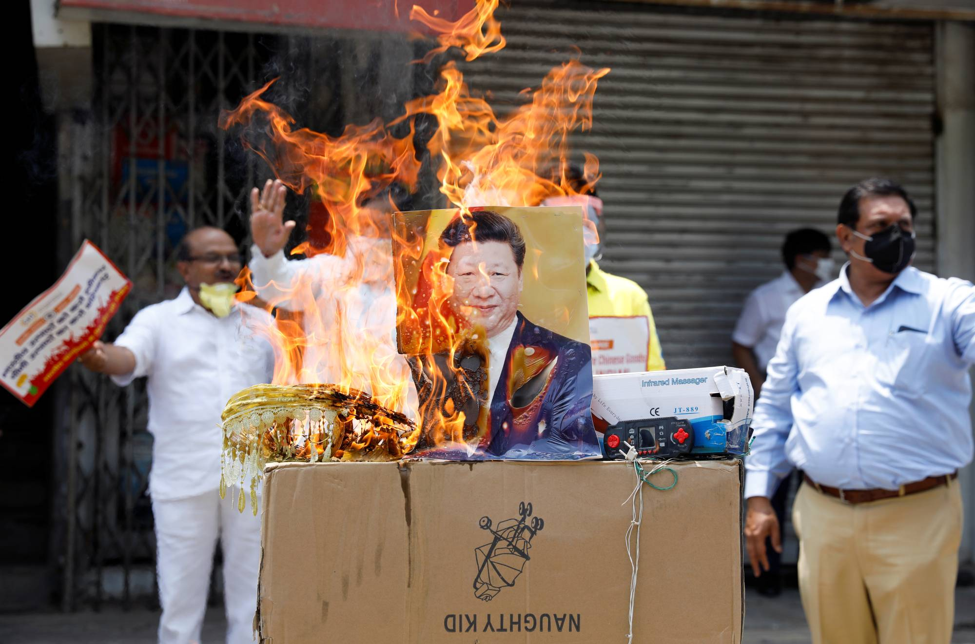 Demonstrators burn products made in China and a defaced poster of Chinese President Xi Jinping during a protest in New Delhi last June. | REUTERS