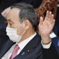 Prime Minister Yoshihide Suga raises his hand during a Lower House Budget Committee session in Tokyo on Tuesday. | KYODO