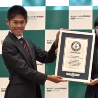 Kawauchi receives a certificate from Kaoru Ishikawa, the country manager of Guinness World Records Japan, during a news conference on Tuesday. | KAZ NAGATSUKA