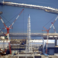 An exhaust stack (center) for the Nos. 1 and 2 reactors of the Fukushima No. 1 nuclear power plant is dismantled in August 2019. | KYODO