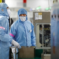 Employees work at a factory run by Renesas Semiconductor Co. in Beijing, in May last year. | REUTERS