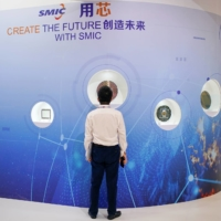 A man visits a booth operated by Semiconductor Manufacturing International Corp. (SMIC) at an exhibition in Shanghai in October. | REUTERS