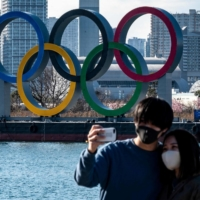 A couple pose for photos in front of the Olympic rings on display at the Odaiba waterfront in Tokyo on February 24, 2021. | AFP-JIJI