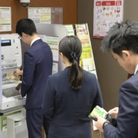 People stand in line at an ATM in Tokyo. | KYODO