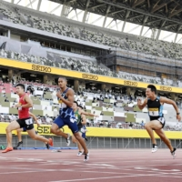 An athletics meet takes place without spectators at Tokyo's National Stadium last August. Japan is facing many unanswered questions about how to hold the Olympic Games this summer amid the coronavirus pandemic. | KYODO