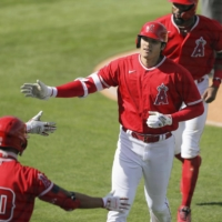 The Angels' Shohei Ohtani is congratulated by teammates after hitting a two-run home run against the Rangers in Tempe, Arizona, on Wednesday. | KYODO