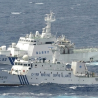 A Chinese marine surveillance vessel sails next to a Japan Coast Guard patrol ship in the East China Sea in September 2012. | KYODO