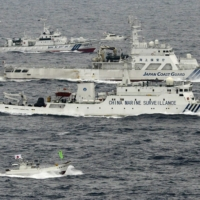 The Chinese marine surveillance ship Haijian No. 66 (center) sails next to Japan Coast Guard patrol ships in the East China Sea near the Senkaku Islands in April 2013. | KYODO