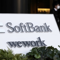 Signage for SoftBank Corp. and WeWork Companies Inc. outside the Tokyo Portcity Takeshiba building, which houses SoftBank Group's headquarters, in Tokyo. | BLOOMBERG