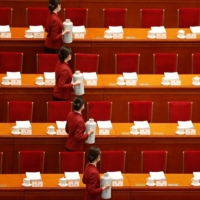Attendants serve tea before the opening session of the National People's Congress at the Great Hall of the People in Beijing on Friday. | REUTERS