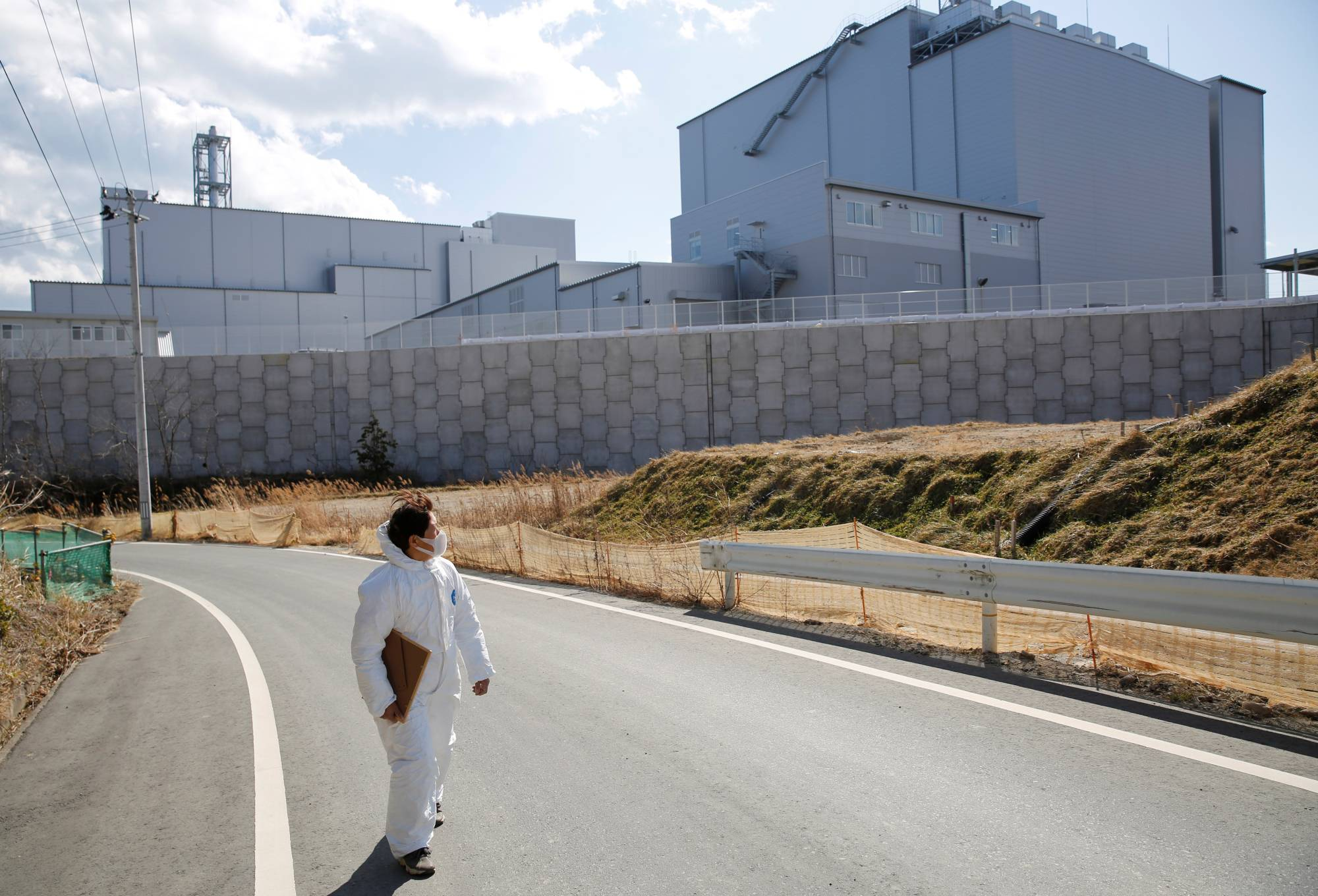 Hisae Unuma wears a protective suit as she walks past an incinerator which was built in a rural village near her collapsing home, where she lived before being evacuated. | REUTERS