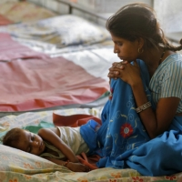 A mother watches over her malnourished child in the Nutritional Rehabilitation Centre of Sheopur district in the central Indian state of Madhya Pradesh in April 2010. | REUTERS