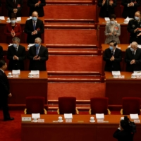 Hong Kong Chief Executive Carrie Lam and other Chinese officials applaud as Chinese President Xi Jinping arrives for the opening session of the National People's Congress at the Great Hall of the People in Beijing on Friday. | REUTERS